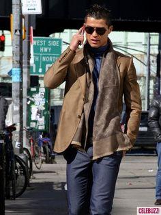 Se llama Christiano Ronaldo. Él es de Santo António, Portugal. Él lleve un chaqueta café, una bufanda café, un suéter azul, y unos jeans. Él lleve unas gafas del sol negras también.
