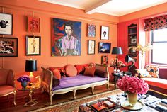 A purple duchesse satin developed for dresses in his studio covers a gilded settee in the uptown apartment owned by fashion designer Zac Posen, whose portrait hangs above the settee, surrounded by a lifetime of artwork and antique knickknacks—which against the coral red walls evokes the feeling of being in a jewel box.