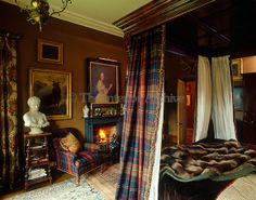 four-poster bed has been hung with tartan curtains .Vincent Knapp/The Interior Archive