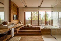 Sala de banho: a banheira foi instalada em plataforma para ficar no nível do terraço. A madeira de demolição cobre a parte seca do piso e compõe a bancada acoplada ao painel na parede. Toalhas, da Mundo do Enxoval. (Foto: Edu Castello)