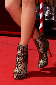 A close up of shoes worn by a model designed by Christian Louboutin at 'Le Carrosse Noir And The Loubi's Angels' presented by Christian Loub...