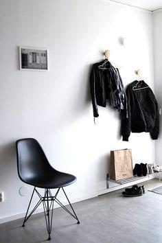 Piso de cimento queimado, cadeira preta Charles Eames, penduradores de parede, sapateira de parede, quadro com moldura branca.