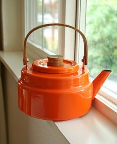 I love tea kettles.  I have a hard time deciding on just one to use in my kitchen.  There are so many pretty and unique ones from which to choose.   orange enamelware tea kettle