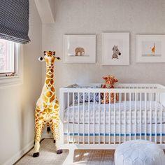 white and cream nursery. faux bois wallpaper, white crib and pouf, animal prints, oversized giraffe, and black polka dot venetian blinds