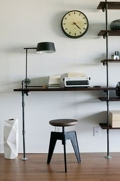 Probably the most classic and elegantly minimal way to set up space for writing.  Nice touch with the clock and stool.