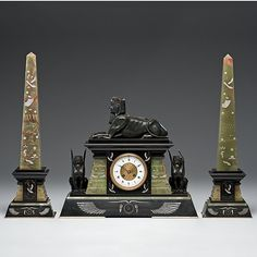 Egyptian Revival Clock Garniture French, ca 19th century. An Egyptian Revival clock with two matching obelisks, unsigned, eight day time and strike, black slate and green onyx;  ht. 17 in.