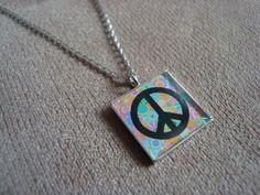 """Colar em metal, na cor prata, com pingentinho de metal com imagem do símbolo """"Paz e Amor"""" em fundo floral, protegida por resina transparente. R$20,00"""