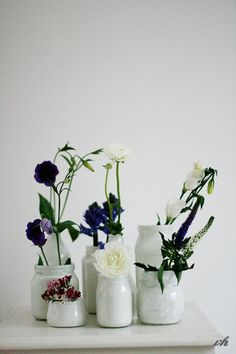 You could paint thrift store or recycled bottles white, and use in a wedding centerpiece like this one.