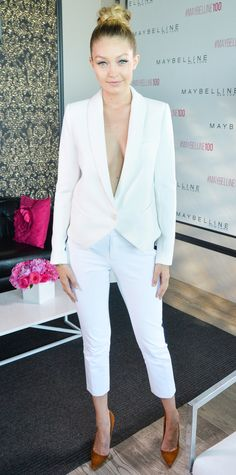 Gigi Hadid suited up for the Maybelline New York 100th Anniversary Party in a smart white blazer (sans layers) and tuxedo-stripe cropped trousers, both by Smythe, with tan suede pumps.