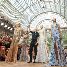 "Julien Macdonald showed a range of slim-fitting pencil dresses, ruffled swimsuits and babydoll shift dresses in his Spring/Summer 2015 collection which had a theme of flowers mixed with tattoos. The Welsh designer revealed that his inspiration was a mermaid who lives in a tropical sea and ""lures a very handsome man"", perhaps similar to the sea nymphs in Greek mythology that lured sailors to their drowning deaths.  <big><em><strong>""My bride is a mermaid that swims in the sea, covered in ..."