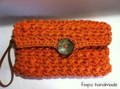Clutch de mão em crochê produzida com fio de malha reciclado. Forrada em tecido de algodão. A alça pode ser removida.