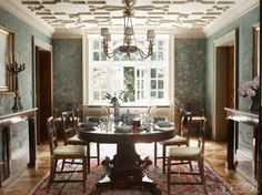 The 19th-century dining table and chairs, with cushions in a Bennison fabric, are Italian, as are the 19th-century consoles and chandelier; the wood door frames are painted in faux marble, the antique painted chinoiserie wallpaper was duplicated by craftsmen in some sections, and the 19th-century rug is Persian.   - ELLEDecor.com