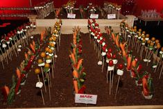 "Edible Garden using toasted pumpernickel crumbs as ""dirt"" with spears of baby carrots, asparagus spears, and zucchini, as well as baby tomatoes and buffalo mozzarella ""flowers."""