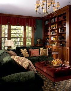 Nice use of dark green and reds make this living room area warm and comfortable paired with the mellow wood built-in shelves and books. Good lighting by a trio of multi-pane windows softly draped.