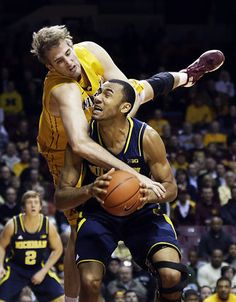 Minnesota's Elliott Eliason comes down on Michigan's Jon Horford for a foul during the first half of an NCAA college basketball game Thursday, Jan. 2, 2014, in Minneapolis.