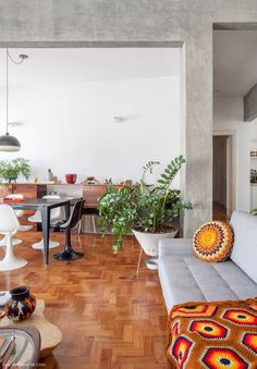 Sala de estar com piso de tacos, vigas de concreto e decoração que mistura móveis contemporâneos, vintage e muitas plantas.