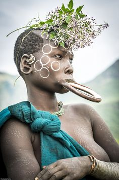 Suri tribeswomen, like the one above, are famous for inserting clay plates in to the lower lip and often decorate themselves with the local flowers and clay patterns