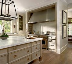 contrast island in a light gray finish. Carerra marble countertops.