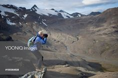 Yooniq images - A woman on a cliff photographs South Georgia Island scenery.