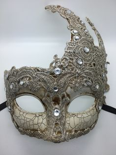 Antiqued Mardi Gras mask with rhinestones and macrame lace. Ribbon ties. Color or tint mat vary a bit. Each one is a little different.
