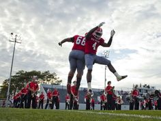 Port Huron's Davhon Washington and Larenz Brown jump in the air as they are introduced during a football game August 29, 2014 at Port Huron High School.