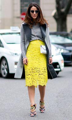 Street style look com casaco cinza e saia renda amarela.