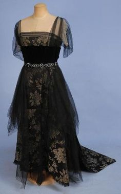 SILK and LAME EVENING DRESS, c.1908. Black satin with gold lame roses, bodice having square neckline with black net sleeve over cream chiffon, black velvet midriff band decorated at the waist, back and shoulder with jet, steel and crystal beads, net over-skirt and asymmetrical train. New York label. by loretta