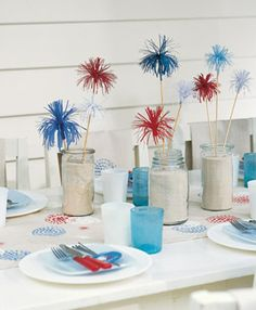 """Fill jars with sand and stick in skewers with present toppers inside to create a """"firework"""" centerpiece."""