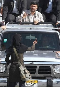 "A brave woman showing the ""FUCK YOU"" gesture to the misogynistic, Iranian president, Mahmoud Ahmadinejad. She is a hero to supporters of women's rights around the world."