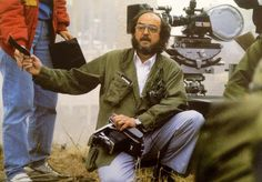 """Kubrick in action. Handing off a Polaroid to an assistant while keeping his eye on the set of """"Full Metal Jacket""""."""