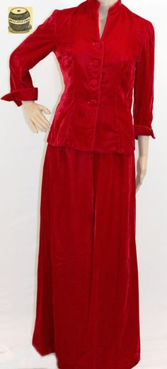Red velvet fitted jacket and floor length skirt. Banded collar with gathered bracelet length sleeves and cloth button enclosure. Handmade