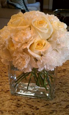 Roses and carnations in clear vases. We can tie a nice ribbon with a little bling around it. Adding the carnations keeps the price down and makes the vase look nice and full.