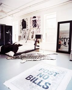 Bedroom area of a large loft with zebra print hide and black and white palette.