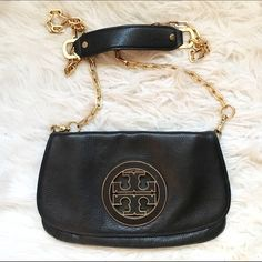 Tory Burch Amanda Logo Clutch Gorgeous buttery black leather crossbody. Minor flattening around the edges of the leather and very light wear on the patina of the chain/hardware. See upclose pics. Interior is clean with a light mark and noticeable wear on the patina of the TB logo on the inside. Also missing the interior pocket zipper pull. Overall great condition! See other listing for more pics. Tory Burch Bags