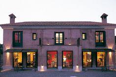 Casa en el Valle de Pungo, La Cumbre, provincia de Córdoba, Argentina, con grandes ventanales, luces puntuales para exteriores y dos chimeneas.