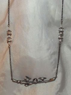 This is a hand crafted family of birds,the parent birds watching over there nest of un hatched baby's. This piece is a pewter colored metal ,i added little pearls to look like eggs,hung it from a silver tone chain that i split with clear rondel cut swarvoskis with star burst spacers. $20
