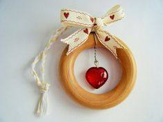 Up cycled wooden curtain ring with red glass heart hanging decoration, cream bow with red heart, and white and gold hanging loop. Hanging loop is