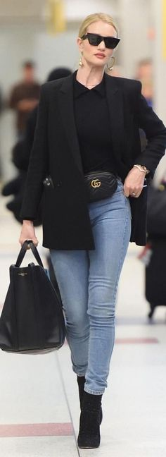 Who made Rosie Huntington-Whiteley's black sunglasses, gold jewelry, belt bag, belted blazer, shirt, tote bag, and ankle boots?