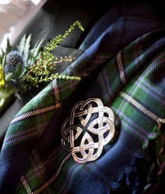 Thistle boutonniere and celtic pin against tartan, worn by the groom at a Scottish wedding.
