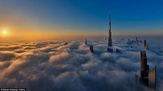 The Burj Khalifa, more than 160 storeys tall, pierces through the fog as a new day begins ...