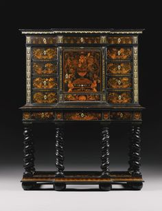 A pewter, brass, fruitwood and stained sycamore inlaid marquetry, ebony and ebonised cabinet on stand attributed to Pierre Gole (1620-1684) Louis XIV, circa 1680 the upper section of breakfront form with three frieze drawers inlaid with lunettes and bellflowers above a cupboard door inlaid with a vase of flowers on a plinth opening to reveal a fitted interior with four drawers and a parquetry floor above a further drawer flanked by panels with a ribbon-tied floral bouquet