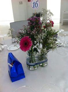 Centros de mesa con flores naturales y la bolsita contiene cámaras desechables y pergamino con instrucciones.