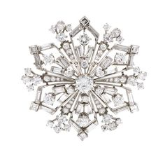 A Platinum and Diamond Snowflake Brooch,  in a geometric open wirework design…