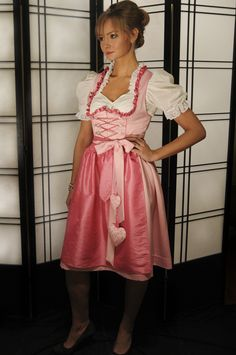 """Love Dirndl - Satin medi dirndl with pink taffeta ruffle surrounding the deep scoop neckline of the chain and ribbon lace up bodice with """"love"""" zipper charm. The apron is also made of pink taffeta with taffeta and satin ties that accent the hanging hearts that feature the breast cancer awareness ribbon.    raredirndl.com to shop"""