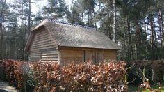 Eiken dubbele carport met aan de achterzijde een eiken schuifdeur. Afgewerkt met een rieten dak.