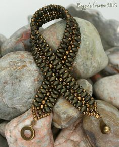 This creation is 2/5mm Metallic Suede Dark Green Superduos embellished with 8/0 Gilded Marble Black and 11/0 Gilded Marble Black Toho Beads.