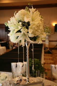 White lily, white hydrangea, white roses, white stock and white tulips were elevated on a silver crystal stand. Streamers of ribbon and crystals completed the design. Photography by Joylyn Hannans. Photo by Holly Chapple Flowers - http://thefullbouquetblog.com/