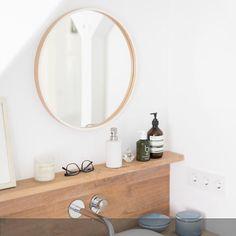 Der runde Spiegel über dem hölzernen Waschtisch passt perfekt ins Badezimmer! Wohnlich wird der Raum durch die natürlichen und zurückhaltenden Materialien. #roomido Mehr auf roomido.com