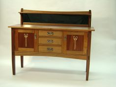 This sideboard was made from African mahogany and features inlay of figured maple and black walnut on each of the two doors.