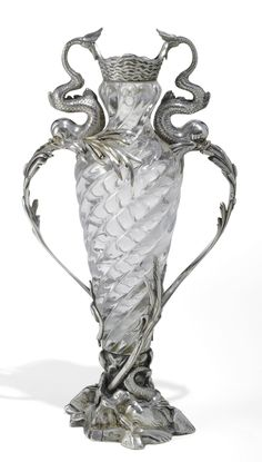 A FABERGÉ SILVER-MOUNTED GLASS VASE, MOSCOW, CIRCA 1893    the amphora form body moulded with swirling gadroons below a wave-chased rim, the handles cast and chased as addorsed squiggle-tailed dolphins issuing bullrush clusters,the rockwork base with a further dolphin and water plants, struck K.Fabergé in Cyrillic beneath the Imperial Warrant, 84 standard, scratched inventory number 5962  height: 32cm, 12 5/8 i